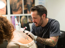 Master doing colorful tattoo on female client's leg stock photo