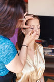 Master doing make up for young beautiful bride Stock Photos