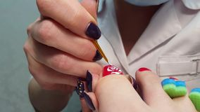 Master Draws a rose on thumb nail - pedicure stock video footage