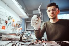 Master of electronic technology holds a chip of broken tablet in the repair shop. Master of electronic technology holds chip of broken tablet in the repair shop stock photography