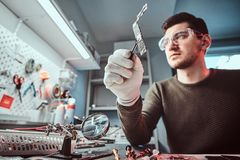 Master of electronic technology holds a chip of broken tablet in the repair shop. Master of electronic technology holds chip of broken tablet in the repair shop stock images