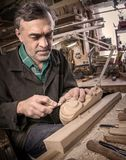 Master examines wood carvings, the carpenter checks the finished. Work stock photography