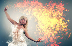 Master fire and water. Fire and water collide. Woman controls both fire and water Royalty Free Stock Photo