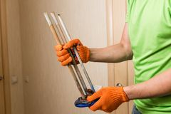 Plumber hands hold old rusty heat element. Master fix water heater and take out spare parts royalty free stock image
