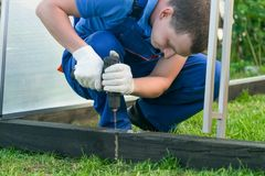 The master fixes the foundation of wood with screws, in the open air stock photography