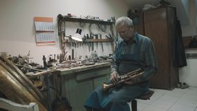 Master in glasses and apron work with brass tuba and instruments in workshop stock footage