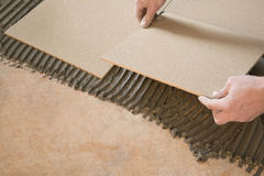 Master glue tiles. Placing terracotta tiles on the adhesive Stock Image