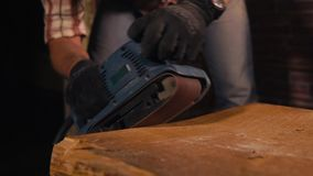 Woodworker is sanding edge of old timber with polishing machine in a factory stock video footage