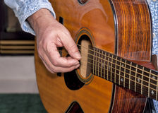 Master guitarist plucks the strings of a guitar Stock Photography