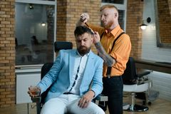 Master hairdresser does hairstyle and style with scissors and comb. Portrait of stylish man beard. Hair Stylist and. Master hairdresser does hairstyle and style royalty free stock images