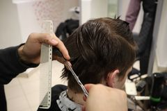 Master hairdresser does hairstyle and style with scissors and comb. Master stacks hair of men in barbershop, hairdresser makes hai stock images