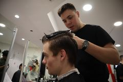 Master hairdresser does hairstyle and style with scissors and comb. Master stacks hair of men in barbershop, hairdresser makes hai stock photo
