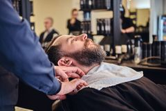 Master hairdresser prepares the face for shaving in the barber shop. Royalty Free Stock Photo