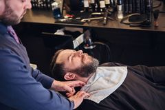 Master hairdresser prepares the face for shaving in the barber shop. Royalty Free Stock Photography