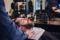 Master hairdresser prepares the face for shaving in the barber shop. Stock Photo