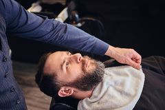 Master hairdresser prepares the face for shaving in the barber shop. Stock Photography