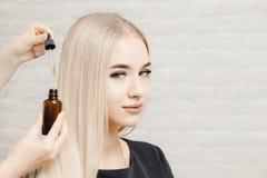 Master hairdresser procedure oil hair treatment for woman. Concept spa salon. Master hairdresser procedure oil hair treatment for woman. Concept spa salon stock image