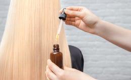 Master hairdresser procedure oil hair treatment for woman. Concept spa salon. Master hairdresser procedure oil hair treatment for woman. Concept spa salon royalty free stock photo