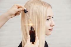 Master hairdresser procedure oil hair treatment for woman. Concept spa salon. Master hairdresser procedure oil hair treatment for woman. Concept spa salon stock photo