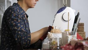 Master of handmade made clothes for doll on sewing mashine. Female master in her studio is engaged handicraft. The process of creating a doll stock footage