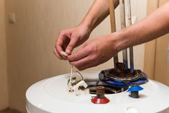 Master hands hold wires of water heater. Process of repair old boiler with rust and corrosion stock photography