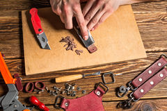 The master holds in his hands a knife and a piece of leather. On brown wooden table scattered with tools and accessories. Photo Royalty Free Stock Image