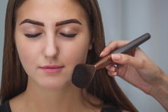 Master inflicts brush powder on the face of the girl, completes Stock Image