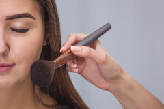 Master inflicts brush powder on the face of the girl, completes the day make-up in a beauty salon. royalty free stock images