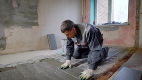 Master is installing floor ceramic tile in a room, pressing down and leveling, interior finishing of premises stock video footage