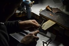 The master jeweler holds the working tool in his hands and makes jewelery at his workplace in the jewelry workshop. stock photography