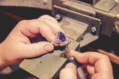 Master jeweler produces a gold ring Stock Photos