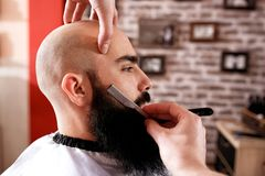 Master makes beards correction in barbershop salon. Men beauty concept royalty free stock images