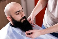 Master makes beards correction in barbershop salon. Men beauty concept royalty free stock photography