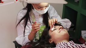 Master makes correction of eyebrows shape in a beauty salon. Master makes correction of eyebrows shape with tweezers for woman in a beauty salon stock video