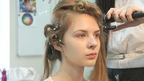 Master makes the curls to girl at the beauty salon stock video