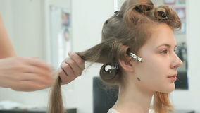 Master makes the curls to girl at the beauty salon stock video footage