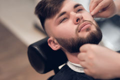 A master makes the depilation thread. The young guy at the barbershop Stock Photos