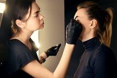 Master makes eyebrows. Eyebrow lamination. The girl makes eyebrows in the salon. Beautiful eyebrow shape. Professional eyebrow stock images