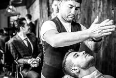 Master makes hair style in barbershop salon. Black-white close up photo. stock photography