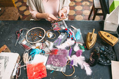 Master makes new  Dreamcatcher in art studio. Craftswoman makes new Dreamcatcher of sewing accessories  in art studio. Top view on workshop table and hands Royalty Free Stock Photo