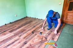 Master makes new floor. Worker master install the laminate floor stock image