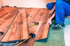 Master makes new laminated floor. Professional master makes new laminated floor stock photography