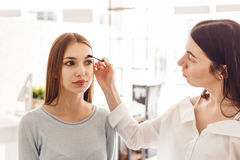 Master makeup corrects, and gives shape for eyebrows in a beauty salon. stock photography