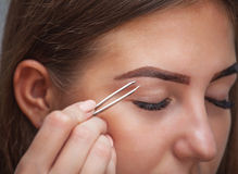 Master makeup corrects, and gives shape to pull out with forceps previously painted with henna eyebrows in a beauty salon. Stock Photos