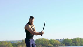 Master making exercise with the sword near the river. Slowly stock footage