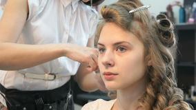Master making hairstyle for the brown-haired girl stock video