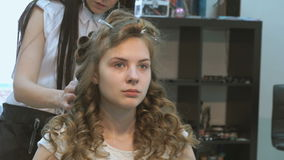Master making hairstyle a girl at the beauty salon stock footage
