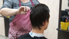 Hairdresser makes hairstyle man. Hairstyling process stock video footage