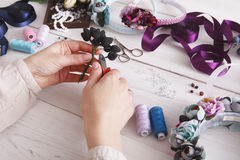 Master making handmade jewelry, woman pov. Needlewoman workplace with plastic beads, flowers and tools for creating accessories Stock Photos