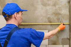 The master measures the distance for lay. The master in the working overalls measures the distance for laying the tiles on the wall royalty free stock photo